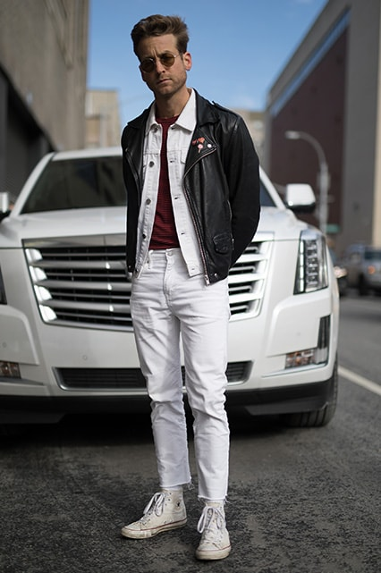 A street-styler wearing a white denim jacket and jeans, a striped T-shirt, a leather jacket and shades | ASOS Style Feed