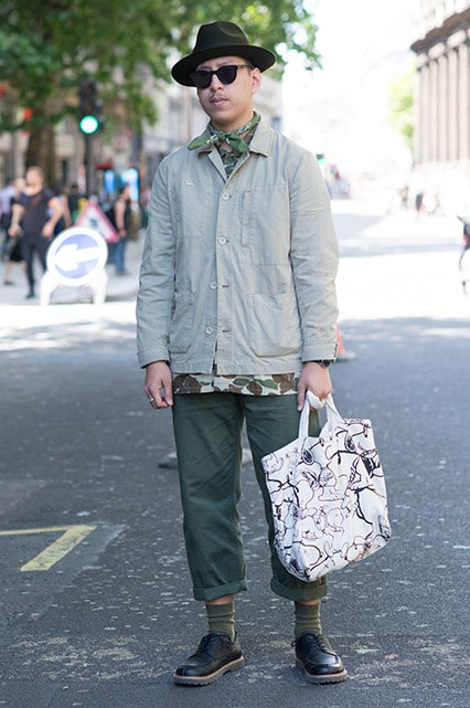 A street-styler wearing a beige coach jacket, scarf, shades, trilby, khaki trousers and lace-up shoes | ASOS Style Feed
