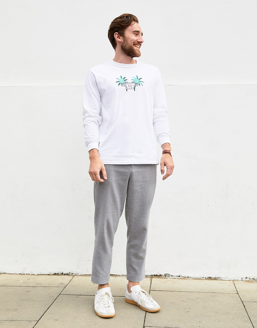 Ashley wearing  a Crooked Tongues long-sleeved tee, grey trousers and white trainers | ASOS Style Feed