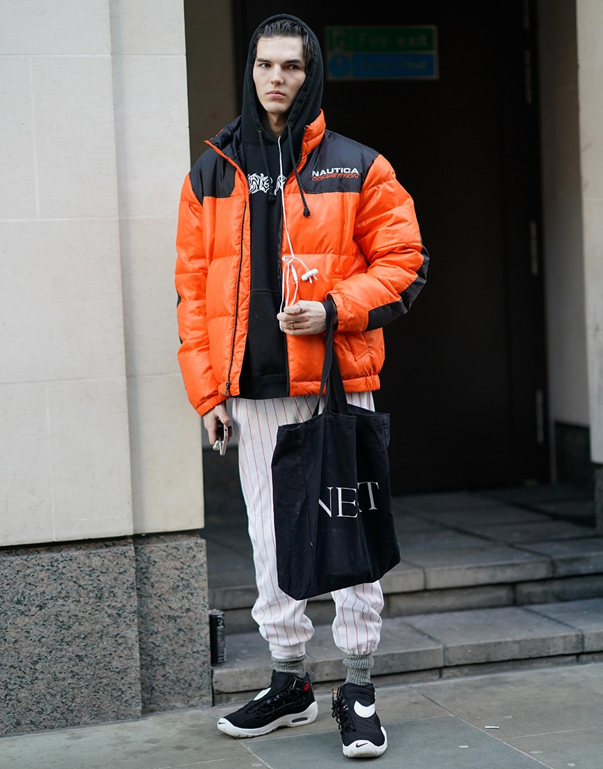 A street-styler wearing a black hoodie, striped trousers, orange puffer jacket and Nike trainers | ASOS Style Feed