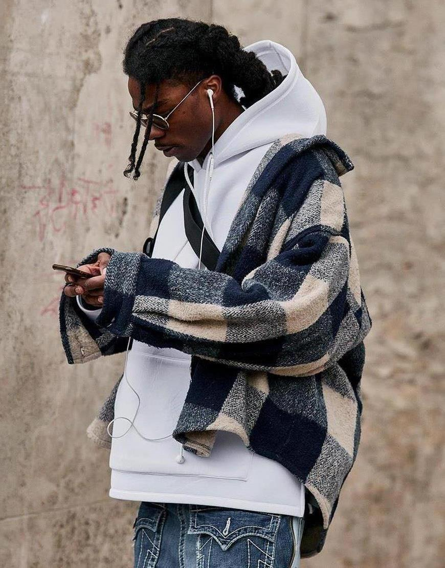 A street-styler wearing a white hoodie, oversized checked jacket and baggy blue jeans | ASOS Style Feed