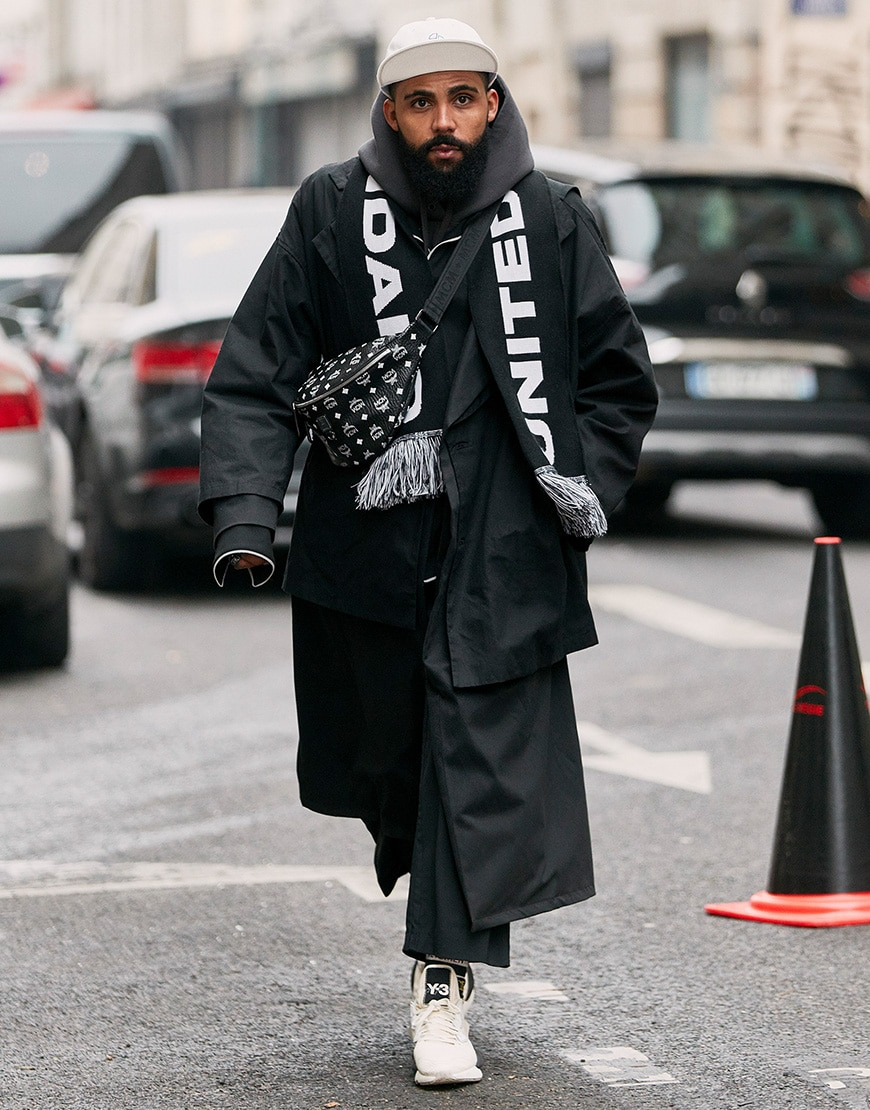 A street-styler wearing an all black 'fit including a cross-body bag and football scarf | ASOS Style Feed