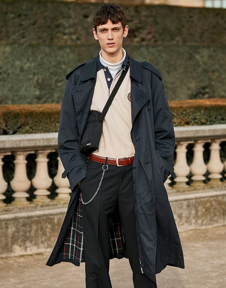 A street-styler in Paris wearing a navy trench coat, cream rugby shirt and dark pinstripe trousers  | ASOS Style Feed
