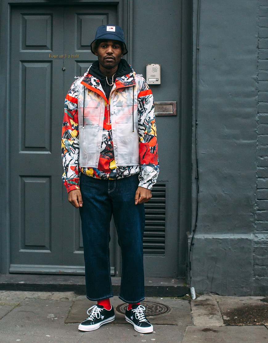A picture of a street style wearing a bright jacket and a bucket hat.