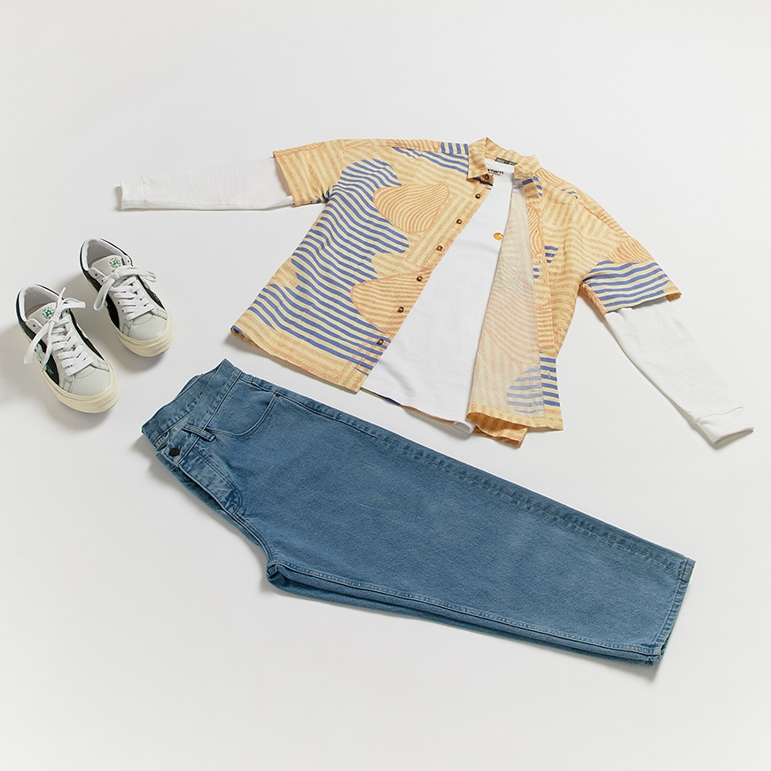 A flat lay outfit of a printed shirt, white T-shirt, wide-cut jeans and Converse Golf Le Fleur trainers. Available at ASOS.