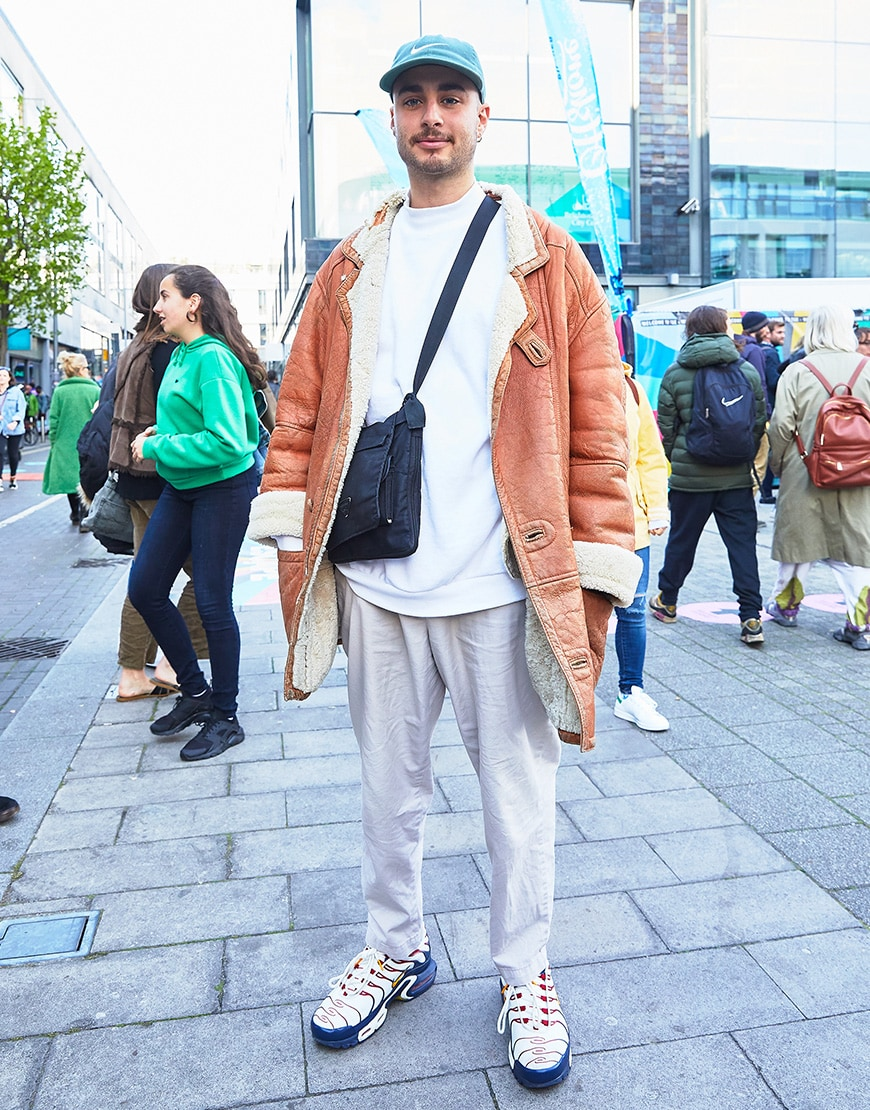A picture of a man wearing a shearling coat, a white sweatshirt and lilac trousers.