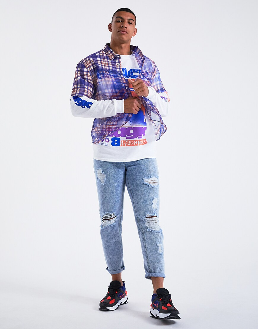 A picture of a model wearing a see-through check shirt over a long-sleeve printed T-shirt with ripped jeans and Nike trainers. Available at ASOS.