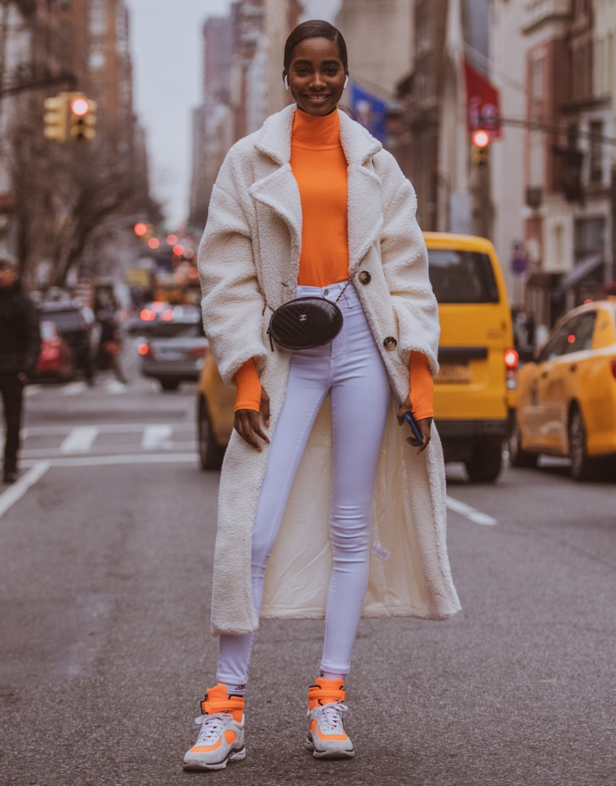 A picture of a female street styler wearing a neon-orange top.