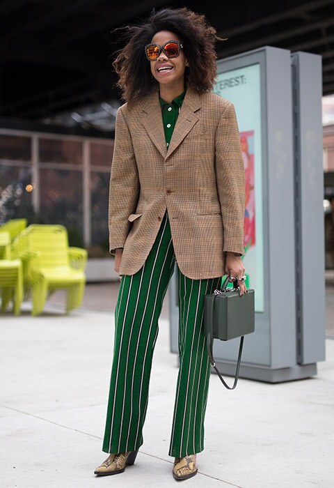 Jan-Michael Quammie attending fashion week wearing a tweed blazer with stripy green trousers and snakeskin boots.