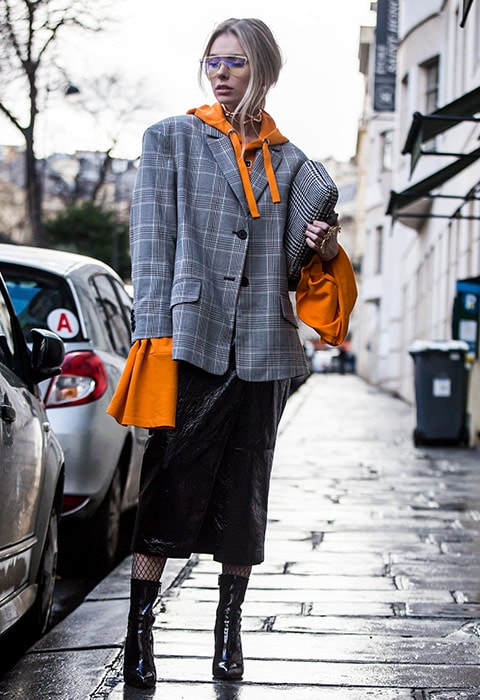 A fashion week attendee wearing an ASOS hoodie with a check blazer, fishnet socks and PVC boots, available at ASOS | ASOS Fashion & Beauty Feed