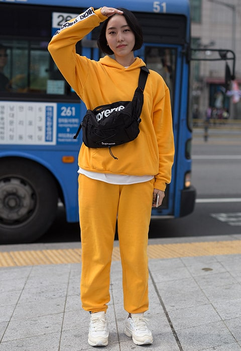 Blogger wearing a yellow tracksuit and Supreme bag | ASOS Fashion & Beauty Feed