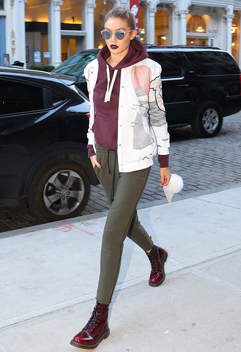 Gigi Hadid wearing a burgundy hoodie, khaki joggers and a statement bomber jacket