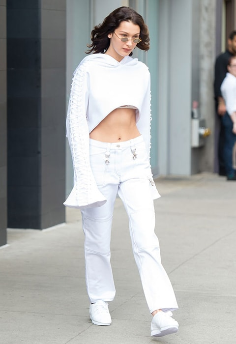 Bella Hadid wearing a white crop top and utility trousers | ASOS Fashion & Beauty Feed