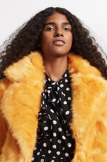 Model Laetitia wearing a mustard faux-fur coat | ASOS Fashion & Beauty Feed